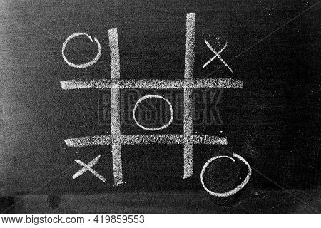 White Color Chalk Hand Drawing As Tic Tac Toe With The Winner And Loser Shape On Blackboard Or Chalk