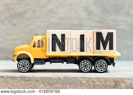 Toy Truck Hold Alphabet Letter Block In Word Nim (abbreviation Of Net Interest Margin) On Wood Backg