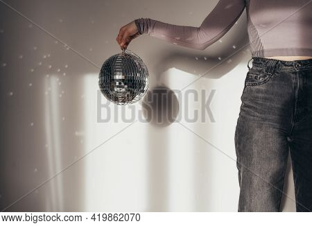 Unrecognizable Woman Holding Disco Ball In Front Of The White Wall
