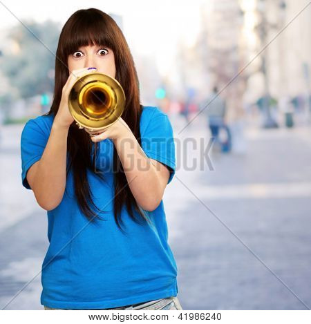 portrait of a teenager playing trumpet, outdoor