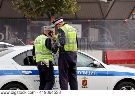 Moscow, Russia - May 2021: Two Traffic Police Officers In Masks Standing Near The Car On The Road. P