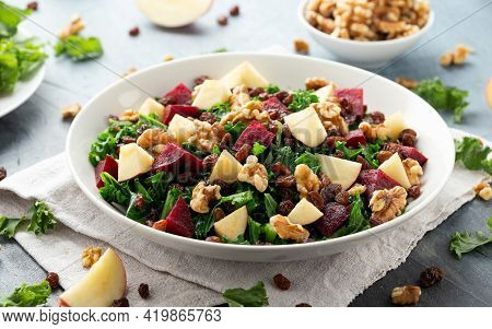 Kale Salad With Apple, Beetroot, Walnut And Raisins In White Plate. Healthy Food