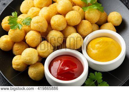 Crispy Potato Balls With Ketchup And Mustard On Black Plate