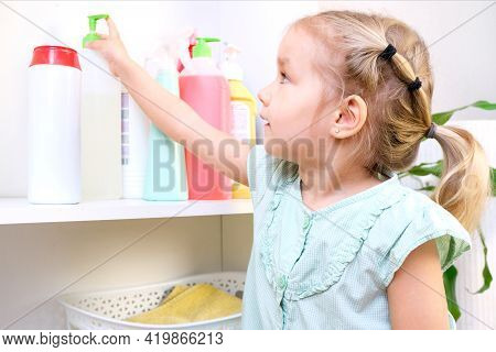 Toddler Touches Bottles Of Household Chemicals, Household Cleaning Products. Dangerous Situation