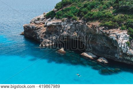 Man Swimming In Cristal Clear Turquoise Ocean Water, Mediterranean Sea, Mallorca, Spain. Cliffs And