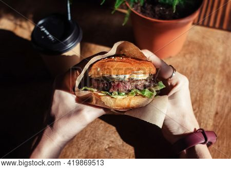 Burger In Paper Packaging, Coffee And Fries Close-up. Food In A Fast Food Restaurant. Macro Photo Of