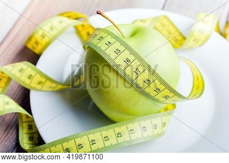 Yellow Measuring Tape Lying On A Green Apple On A Plate - Life Healthy Concept