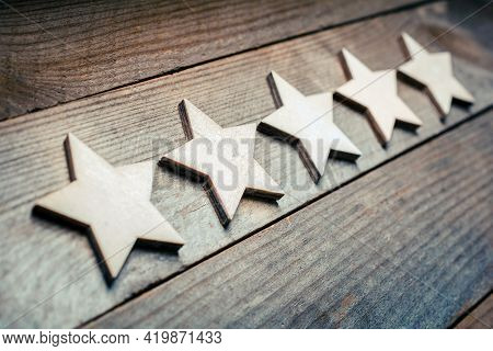 5 Stars Lying On A Wooden Board - Dutch Angle - Quality Concept