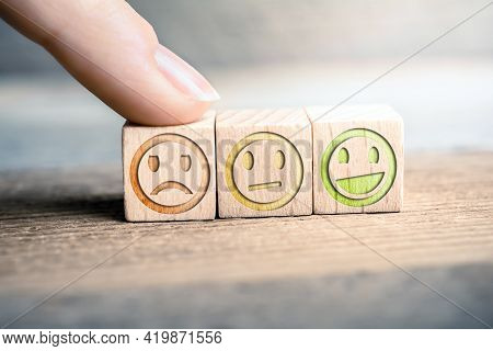 Bad Feedback Concept With Red, Yellow And Green Smiling Faces On Wooden Blocks On A Board, The Red F