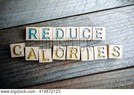 Reduce Calories Written On Wooden Blocks On A Board - Life Healthy Concept