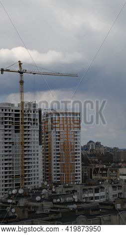 Construction Site Of Unfinished Multistory Building With Crane Jib At Overcast Sky Background. Under