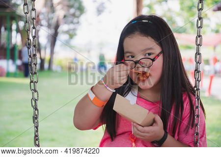 Asian Girl Eats Fast Food From Paper Plate While Sitting On Swing. Young Kid Wearing Eyeglasses. Chi