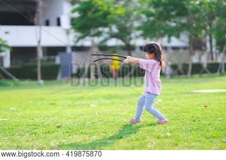 Side View. Asian Girl Running And Having Fun In The Lawn. Kid Took The Pod From The Tree To Play. Ch