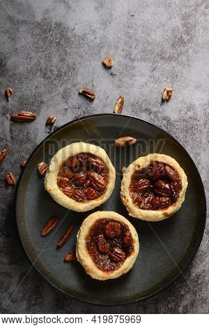Top View Three Pecan Tarts On A Grey Plate With Fresh Nuts