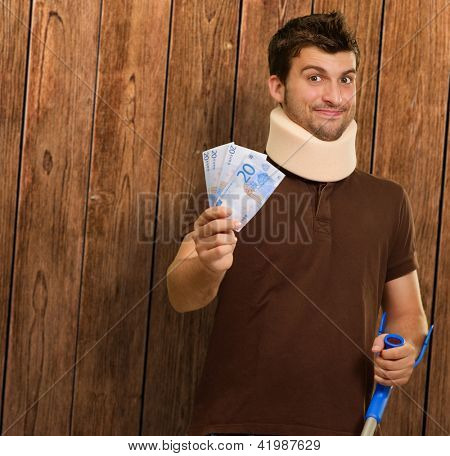 Disabled Man With Neck Brace Holding Euro Note On Wooden Background