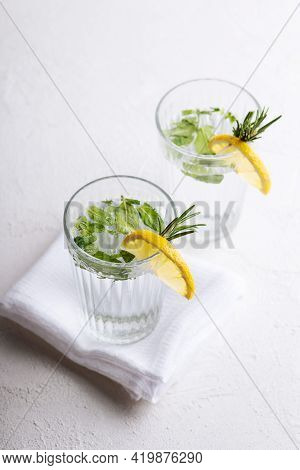 Two Glasses Of Fresh Water With Chopped Mint Leaves, Decorated With Lemon Wedges And A Sprig Of Rose