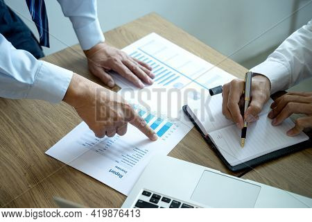 Businessman Point To The Paper Graph To Tell Staff Team About The Marketing Plan