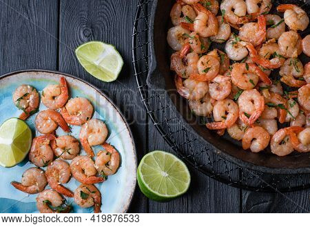 Prawns Fried With Garlic On A Blue Porcelain Plate And In A Black Cast Iron Skillet With A Slice Of