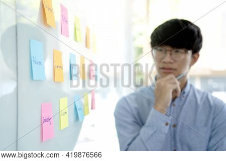 A Businessman Watching The Pose Note Pad On The Glass