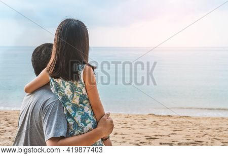 Asian Little Daughter Put Her Hand Over Her Father's Shoulder, Lookin At The Horizon From The Beach,