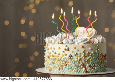 Beautiful Birthday Cake With Burning Candles On Stand Against Festive Lights. Space For Text