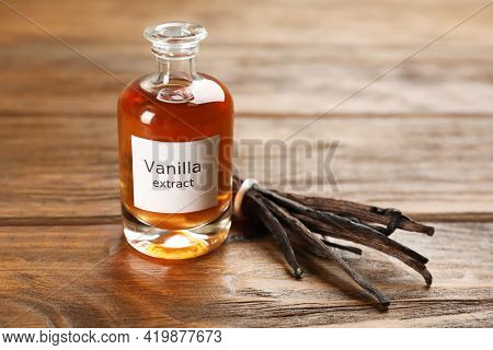 Aromatic Vanilla Extract And Beans On Wooden Table