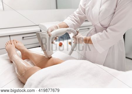 Close Up Of Laser Leg Hair Removal, Beautician At Spa Beauty Clinic Using Hardware Cosmetology Devic