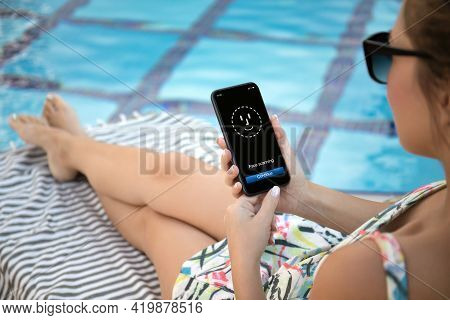Woman Resting By Pool And Holding Phone With Face Id Scanning On Screen