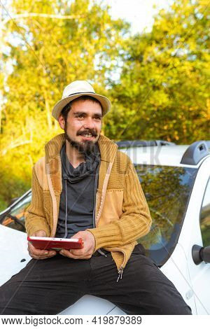 Latino Traveler Man With Sombrero Sitting On The Hood Of His Car And Using Modern Technology To Char