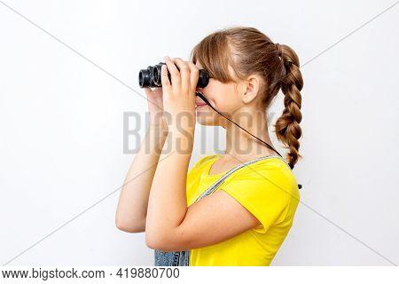 Girl Looking Through A Binoculars. Holding Binoculars Lens