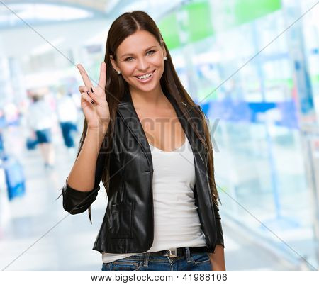 Young Woman Giving Victory Sign, indoor