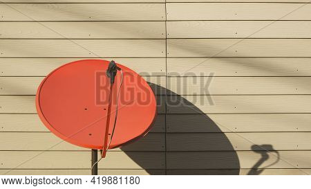 Sunlight And Shadow On Surface Of The Old Red Satellite Dish On Artificial Wooden Wall Background