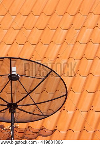 Part Of Satellite Dish On Orange Tile Roof In Vertical Frame