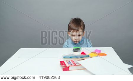 Photo Four Year Old Boy Sculpting In Plasticine On Gray Background