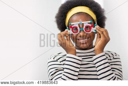 Happy Young Black Woman Checking Vision With Eye Test Glasses During A Medical Examination At The Op