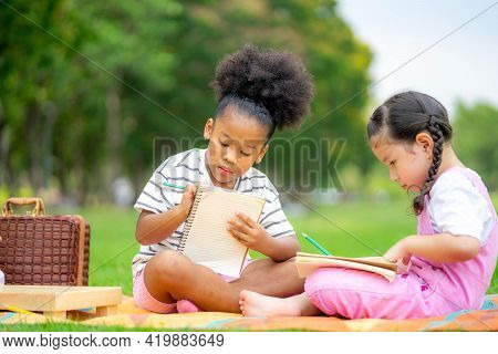 Two Children Lying And Drawing With Colored Pencils At Summer Park, Feel Happiness, Friendship And H