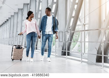 Journey Together. Smiling Black Spouses Walking With Luggage In Airport Terminal