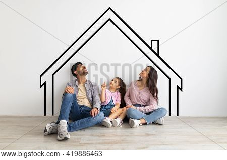 Happy Young Eastern Family Of Three Sitting On Floor And Looking Upwards At Empty Space, Dreaming Ab