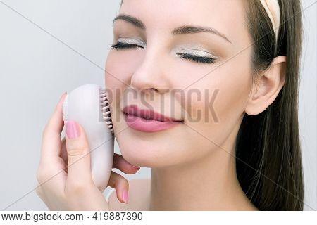 Facial Skin Care Concept. Young Woman Uses Sponge Facial Massager. Pastel Color Photography