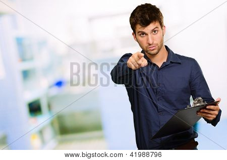 Portrait Of Man Holding Clipboard And Gesturing, Indoors