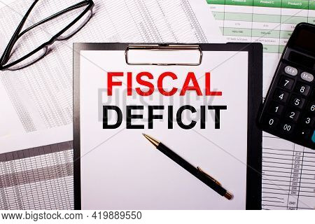 The Words Fiscal Deficit Is Written On A White Sheet Of Paper, Near The Glasses And The Calculator.