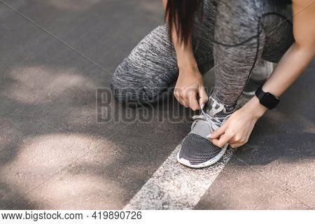 Female Athlete Tying Sports Shoes During Morning Jogging Outdoors
