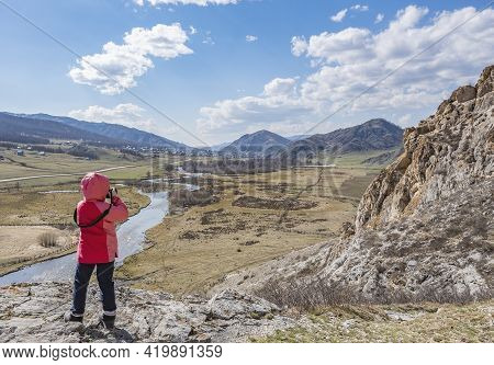A Little Girl, A Child In An Autumn Warm Jacket Stands And Takes Pictures With A Camera Of A Landsca