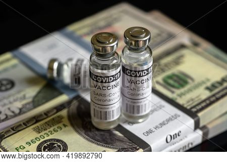 Vaccine Vials From Covid-19 And Dollar Bill Stacks, Bottles With Coronavirus Drug On Us Money Pile.