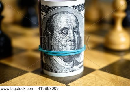 Dollar Banknotes Roll With Franklin On Chessboard, Us Cash And Chess. American Money Bills And Chess