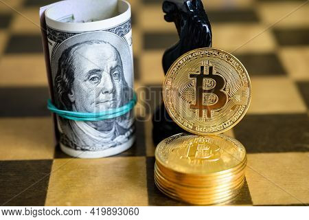 Dollar Bills And Bitcoin Stack On Chessboard. Us Cash, Gold Bit Coins And Chess Figure. Virtual Mone