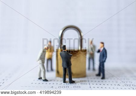 Business And Security Concept. Group Of Businessman Miniature Figure People Standing Around Gold Mas