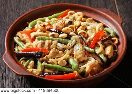 Close-up Of Chicken Satay Rice Noodle With Green Beans, Pepper And Eggplant In A Bowl On A Wooden Ta