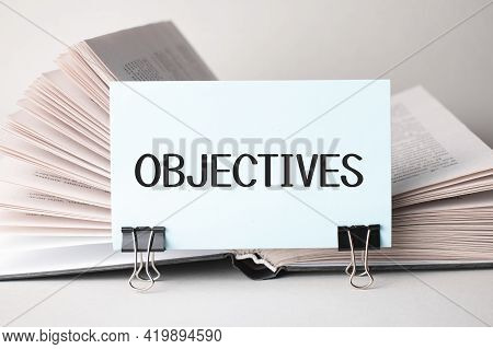 A White Card With The Text Objectives Stands On A Clip For Papers On The Table Against The Backgroun