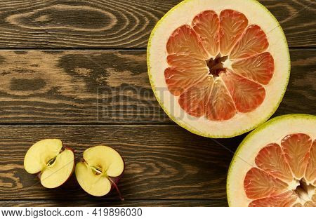 Red Pomelo Halves And Apple Halves On A Wooden Table, With Copy Space